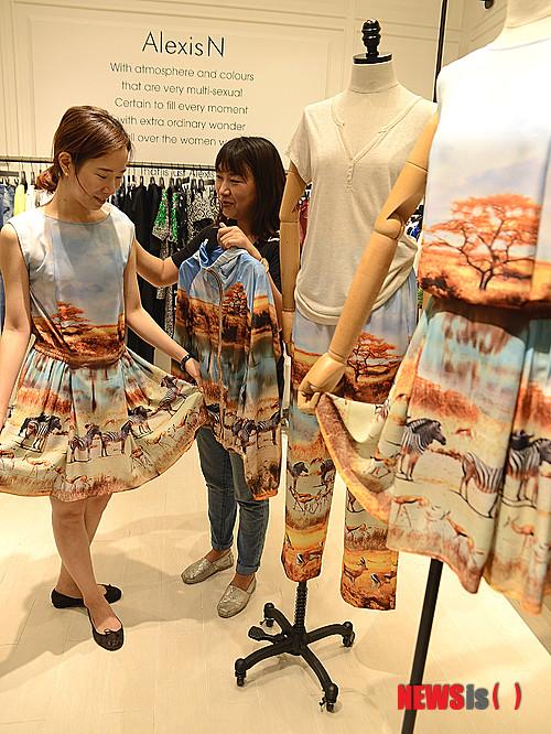 c34f2a3dbfa 【부산=뉴시스】하경민 기자 = 10일 롯데백화점 부산본점 에비뉴엘관의 한 여성복 매장을 찾은 여성들이 아프리카의 넓은 초원이 들어간  다양한 옷을 살펴보고 있다.
